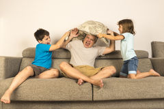 Dad and kids fighting together with pillows Stock Photo
