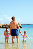 Dad and kids go swimming in the sea. Stock Photography