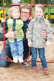 Dad with kids on playground Stock Photo