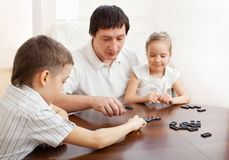Dad with kids plays dominoes Royalty Free Stock Images