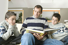 Dad and kids reading book Stock Photo