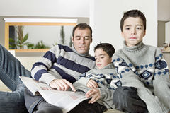 Dad and kids reading magazine Stock Image
