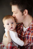 Dad kissing baby. Young father kisses his new daughter stock images