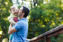 Dad kissing his little daughter on bridge in park Royalty Free Stock Photo