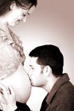 Dad kissing mums belly - monochrome Stock Photography