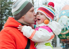 Dad kissing daughter. Dad kissing and soothes daughter outdoors stock image