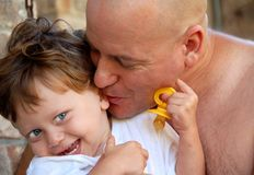 Dad Kissing Toddler Son. Dad and young son bonding over embrace and sweet kiss stock photo