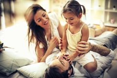 Dad, let`s play. Happy family playing in bed. Space for copy royalty free stock photo
