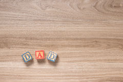DAD letters. Toy blocks on a wooden background Stock Images