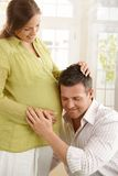 Dad listening to baby in belly Stock Photo