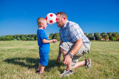 Dad and little boy play with the ball Stock Photos