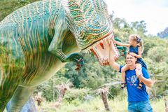 Dad with little daughter near big green dinosaur in the park on a sunny day. Yang Bay, Vietnam stock image