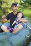 Dad with little daughter sitting in a boat on the river. Royalty Free Stock Photography