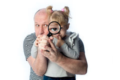 Dad and little girl intently looking Stock Images