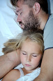 Dad and little girl sleeping together on bed. Dad and little blonde girl sleeping together on bed Royalty Free Stock Images