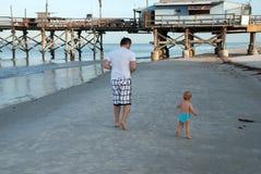 Dad and little son do a morning run, Florida. Dad and little son running along the shore of the Gulf of Mexico, Florida, USA stock photography