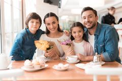 Dad and the little son are giving flowers to mother and daughter in a cafe. A young family came together in a cafe. They celebrate the holiday. Mom, dad and Stock Photography