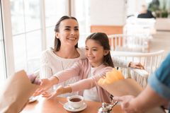 Dad and the little son are giving flowers to mother and daughter in a cafe. A young family came together in a cafe. They celebrate the holiday. Mom, dad and Stock Image