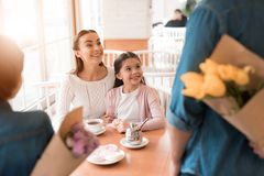 Dad and the little son are giving flowers to mother and daughter in a cafe. A young family came together in a cafe. They celebrate the holiday. Mom, dad and Royalty Free Stock Photos