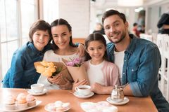 Dad and the little son are giving flowers to mother and daughter in a cafe. Stock Photography