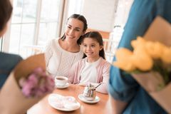 Dad and the little son are giving flowers to mother and daughter in a cafe. A young family came together in a cafe. They celebrate the holiday. Mom, dad and Royalty Free Stock Photography