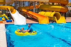 Dad and little son having fun on waterslide. During sun holidays royalty free stock images