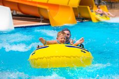 Dad and little son having fun on waterslide. During sun holidays Royalty Free Stock Image