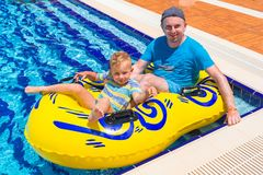 Dad and little son having fun on waterslide. During sun holidays Royalty Free Stock Photography