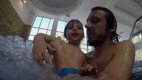 Dad and little son swimming in the indoor pool. At the Spa stock video footage