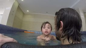 Dad and little son swimming in the indoor pool stock video