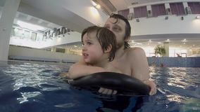 Dad and little son swimming in the indoor pool stock footage