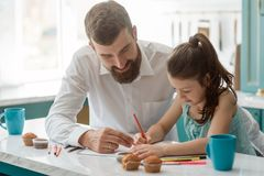 Dad looks his daughter drawing. Dad looks at his daughter drawing with color pencils. Creative activity to make a bond between parents and children royalty free stock image