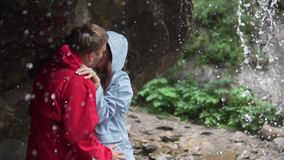 Dad lovers in jackets stand under the water of the waterfall and kiss passionately. A man and a woman are standing under a waterfall and kissing. Dad lovers in stock video