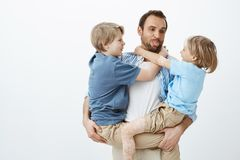 Dad loves spending time with family. Carefree happy father holding sons in arms and sticking out tongue, making faces. And enjoying playing with children while royalty free stock image