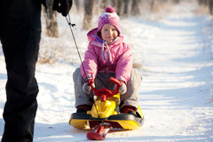 Dad lucky child on a sled Stock Photo