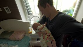 Dad lulling baby daughter at home stock footage