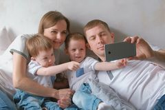 Dad makes family selfie on mobile phone. Mom, dad and two brother twins toddlers. Dad makes family selfie on mobile phone. Mom, dad and two brother twins stock photo