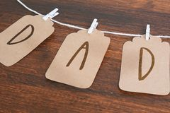 Dad message written on tags hanging on clothespins on wooden bac. Kground. Happy father`s day concept Stock Photos