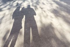 Dad mom and baby. Family shadows on asphalt. Silhouettes of parents and little child stock photography