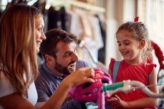 Dad and mom buying new bicycle for little girl in bike shop. Dad and mom buying new bicycle for happy little girl in bike shop royalty free stock images