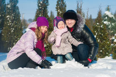 Dad mom and daughter on a background of winter trees and blue sky, lifestyle, winter vacation, fun Stock Photos