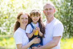 Dad, mom and daughter drink juice from one glass. royalty free stock image
