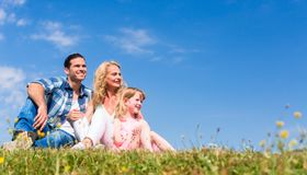 Family sitting in green grass on meadow Royalty Free Stock Image