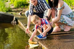 Dad and Mom helps the little boy to lower the paper boat to the. Water. Mom, dad and their little son launch paper boats in a river in the summer royalty free stock image