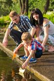Mom, dad and their little son launch paper boats in a river in t. Dad and Mom helps the little boy to lower the paper boat to the water. Mom, dad and their stock images