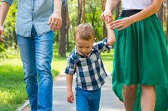 Dad and mom hold their son by the hand and walk along the park r. Oad. Family resting in the park in sunny day Royalty Free Stock Images