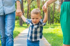 Dad and mom hold their son by the hand and walk along the park r. Oad. Family resting in the park in sunny day Stock Image