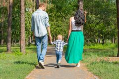 Dad and mom hold their son by the hand and walk along the park r. Oad. Family resting in the park in sunny day stock photography