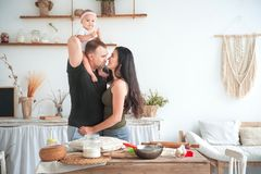 Relationship in the family with small children. Dad and mom kiss in the bright kitchen, children help to cook in the kitchen stock photos