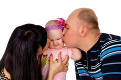 Dad and mom kissing baby Stock Photography